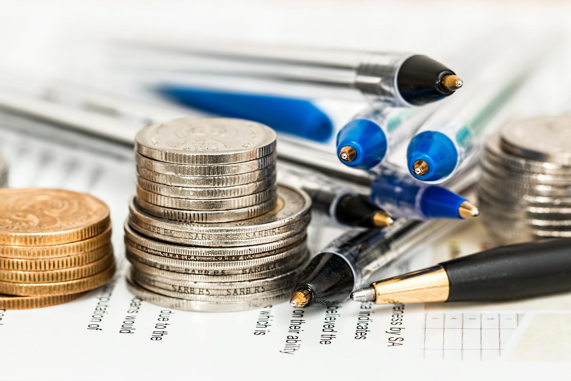 Lokaty terminowe - co to? Długopisy i akcesoria biurowe obok stosu monet