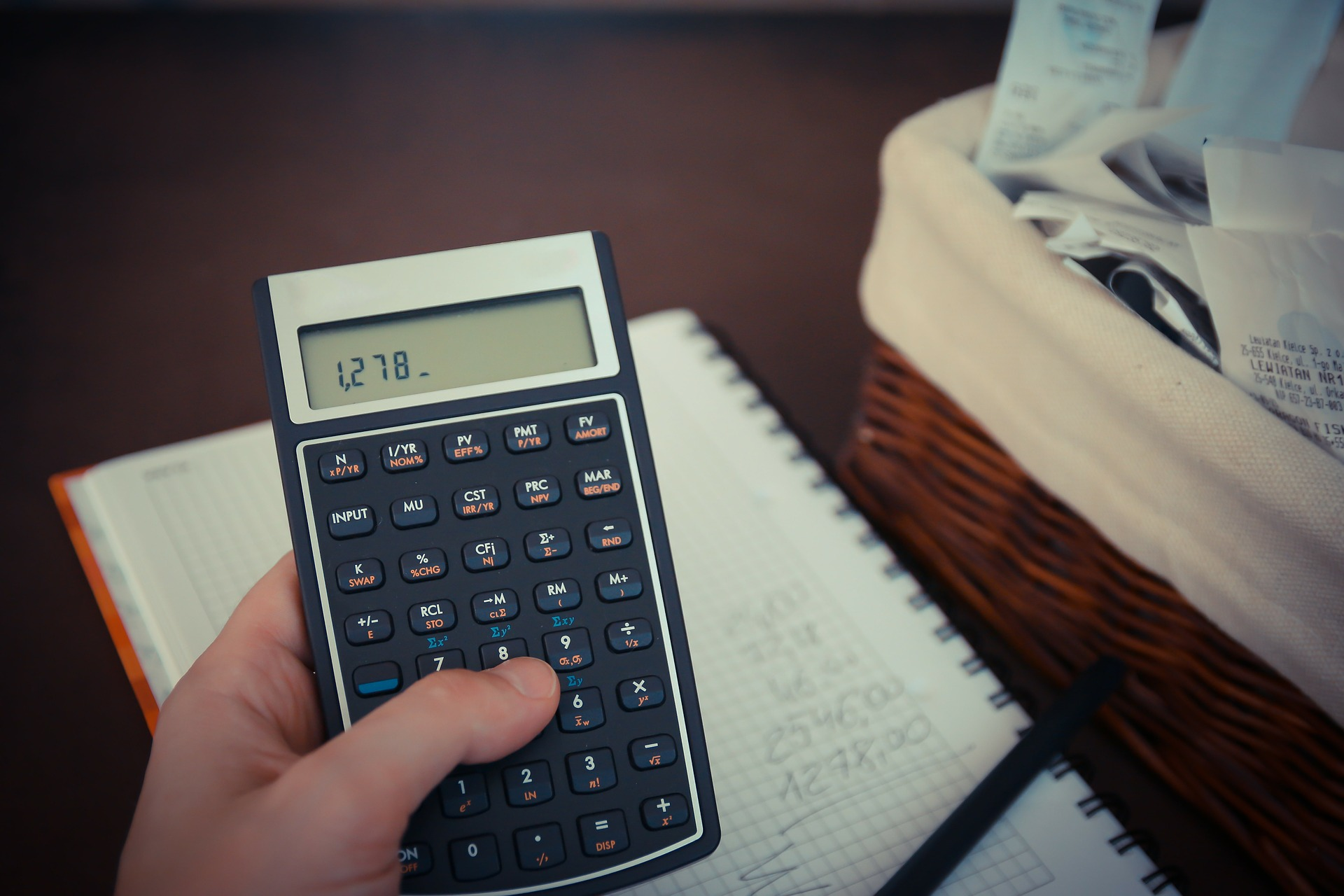 Oprocentowanie kredytu samochodowego; ręka człowieka, który próbuje wyliczyć koszty