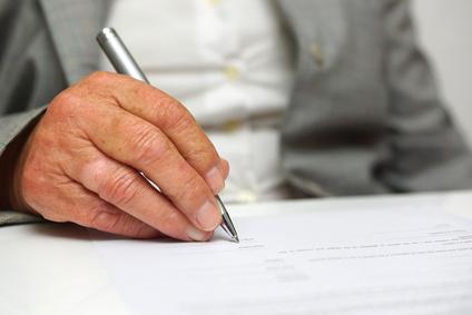 starsza kobieta podpisująca umowę