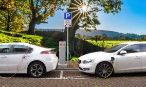 Zdjęcie przedstawiające dwa samohody elektryczne oraz stację ładowania. W tle piękny krajobraz